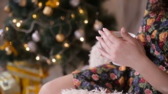 Female hands with tea cup near christmas tree. Beaty girl drinking tea Stock Footage