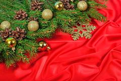 Golden Christmas decorations and spruce branch and cones on a red back Stock Photos