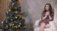 Beautiful girl drinking tea near decorated Christmas tree, sitting in a Stock Footage
