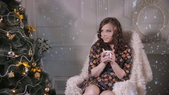 Beautiful girl drinking tea near decorated Christmas tree, sitting in a Arkistovideo