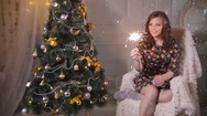 Attractive young woman near christmas tree in chair holding sparkler, bengal Stock Footage