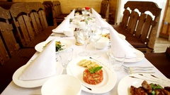 Celebratory table, dishes with a meal on the table, forks glasses, knives Stock Footage