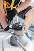 Closeup up of Yachtsman hands dealing with yacht ropes .Lens flare Stock Photos