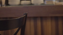 Girl in a black dress goes past the bar stool and touches his hand Stock Footage