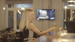 Young blond woman drinking a glass of beer at a bar Stock Footage