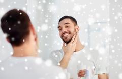 Happy man applying aftershave at bathroom mirror Stock Photos