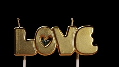 Cake with the word love and burning candles Stock Footage