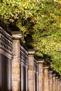 Illuminated ornamental fence of city park Stock Photos