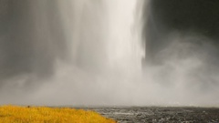 Powerful stream of waterfall is falling on ground and creating river, yellowed Stock Footage