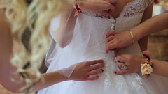 Wedding preparation, wedding gown being tied up by bridesmaid Stock Footage