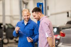 Auto mechanic with clipboard and man at car shop Kuvituskuvat