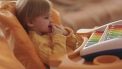 Adorable little girl in a yellow sweater playing with her fingers, and looking Stock Footage