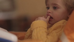A little adorable blue-eyed baby in a stylish yellow sweater playing with her Stock Footage
