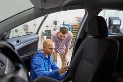 Mechanic and man checking seat belt at car shop Kuvituskuvat