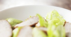Caesar salad closeup camera backwards fly follow falling croutons Stock Footage