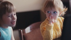 Two little sisters having fun, watching the cartoons. A cute blue-eyed girl Stock Footage