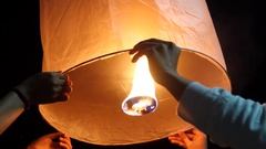 Hands Releasing Floating Lantern at Yee Peng Festival in Chiang Mai, Thailand Stock Footage