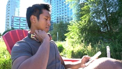 Trendy guy listening to music in park, Long Island Stock Footage