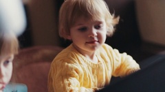 Little blue-eyed baby-girl in a yellow bright sweater having fun with her elder Stock Footage