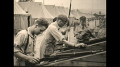Vintage 16mm film, 1943 Soldiers cleaning rifles along tent line Stock Footage