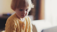 Cute blue-eyed toddler in a bright yellow colored sweater having fun, loudly Stock Footage