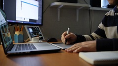 Designer works with image on laptop and using a digital tablet Stock Footage