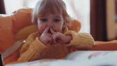 A cute toddler in a bright yellow colored sweater picks her nose while reading Stock Footage