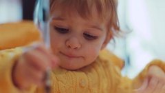A toddler sitting in the high chair painting with pen on the sheet of paper and Stock Footage