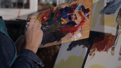 Girl artist paints on the canvas with a brush. close-up on the hands of the Stock Footage