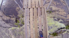 Man walking on the bridge over the mountain river Stock Footage