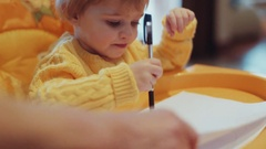 Adorable blue-eyed blonde baby in a bright yellow sweater having fun. A toddler Stock Footage