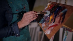 Young female art student mixing paint on palette in art studio with brushes in Stock Footage
