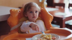 Little blue-eyed blonde baby having breakfast in her cute pajamas. The toddler Stock Footage