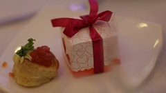 Sweet cake and present in the box with red ribbons on the plate Stock Footage