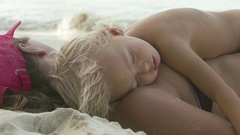 Mother and child sleeping on a tropical beach Stock Footage