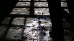 Footsteps of a man walking away in dark shadows room Stock Footage