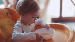 Adorable little blue-eyed blonde baby sitting in the orange high chair in a Stock Footage