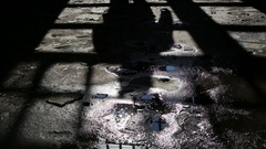 Footsteps of a man slowly moving towards in dark shadows room Stock Footage