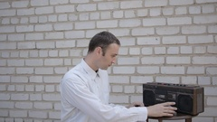 The man inserts the tape into the old cassette player and push play. Stock Footage