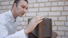 Man blow away the dust from an old cassette recorder. Stock Footage