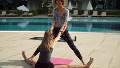 Young female and instructor practicing yoga near the pool slow motion Stock Footage