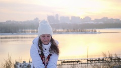 Happy active woman having fun and throwing snow in winter field on sunset city Stock Footage