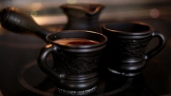 Clay coffee set Cezve and two cups with steaming coffe Stock Footage