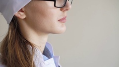 Portrait of a young adult female doctor with glasses, looking at the window Stock Footage