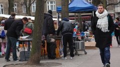 People shop and sell at flea market, pan left, Berlin, Germany Stock Footage
