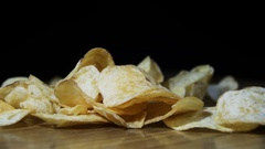 Potato Chips are Falling on a Wooden Table on Black Background in Slow Motion Stock Footage
