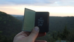 To travel is to live. Book with the inscription. Forest on background Stock Footage