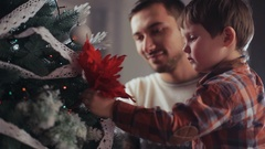 Family portrait, father helping son to decorate Christmas tree. Small boy Stock Footage