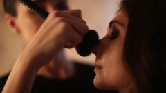 Professional makeup artist putting cosmetics on amazing European girl with a Stock Footage