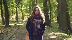 Girl in a romantic look, with curly hairstyle and checkered scarf walking down Stock Footage